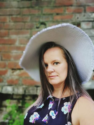 Portrait of mid adult woman wearing hat against wall