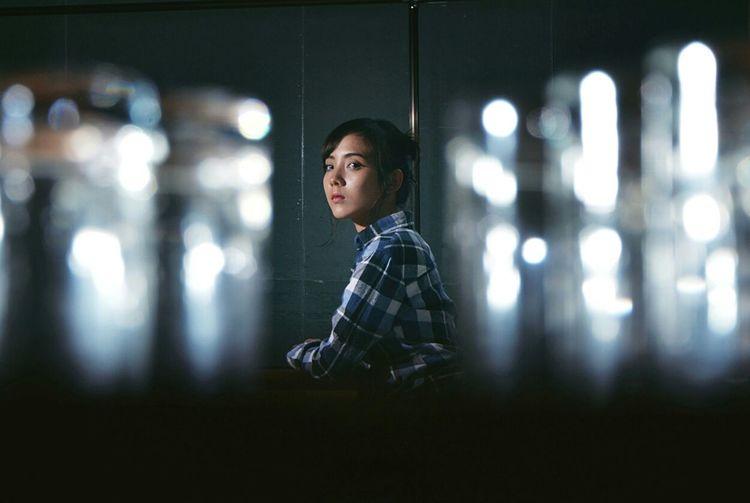 Woman of illuminated lighting equipment at night
