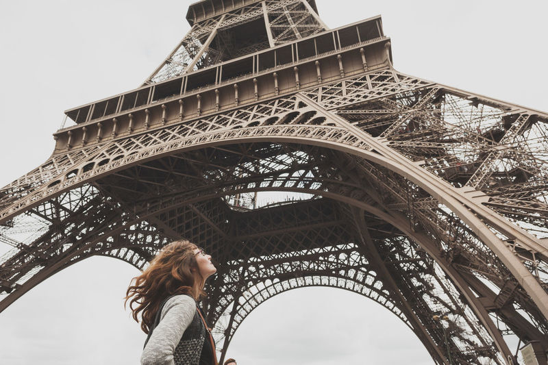Low angle view of woman standing under eiffel tower against sky