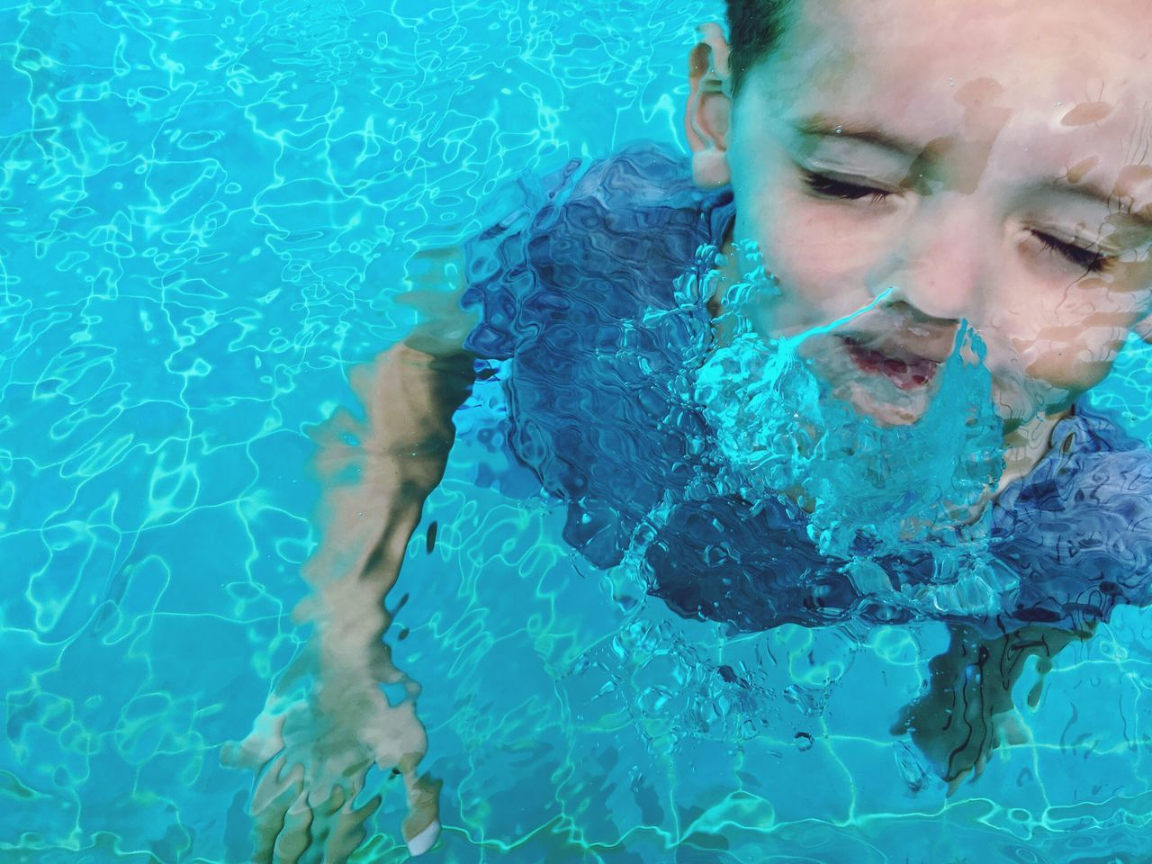 swimming pool, water, real people, one person, young adult, leisure activity, lifestyles, young women, front view, day, outdoors, beautiful woman, headshot, blue, underwater, swimming, portrait, close-up, people