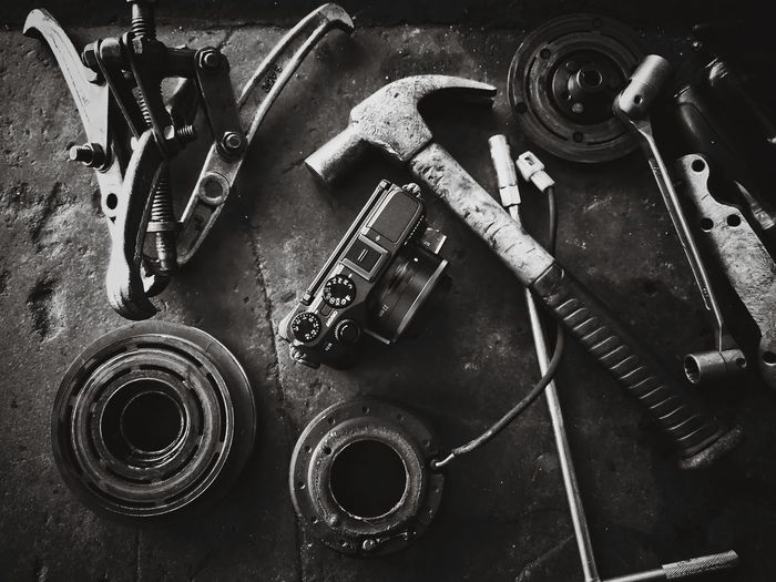 High angle view of hand tools and camera on table