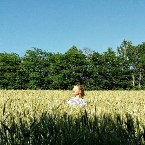 Woman in field against clear blue sky