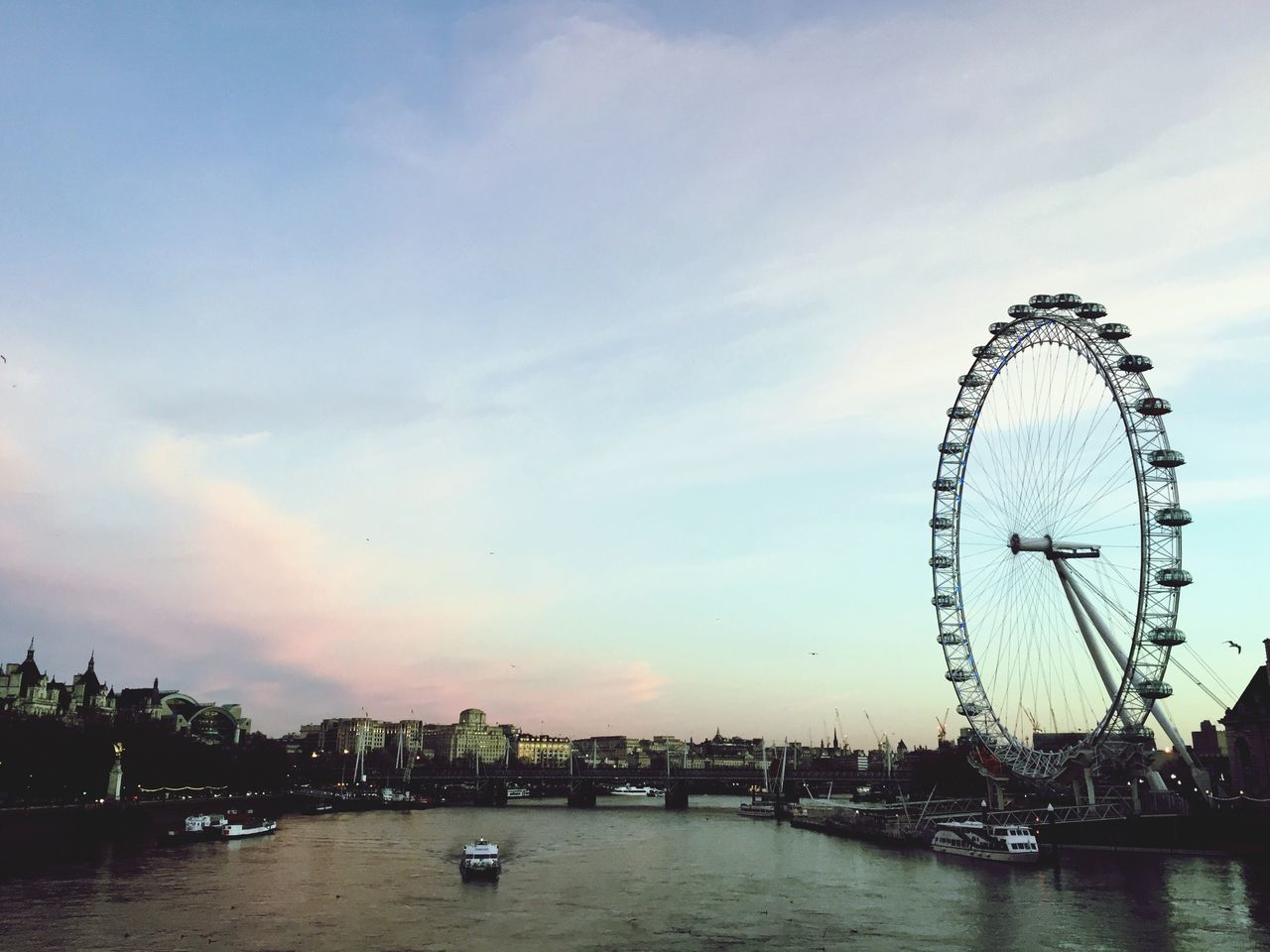 ferris wheel, sky, cloud - sky, arts culture and entertainment, water, nautical vessel, big wheel, travel destinations, outdoors, river, waterfront, built structure, sunset, architecture, building exterior, no people, day, city