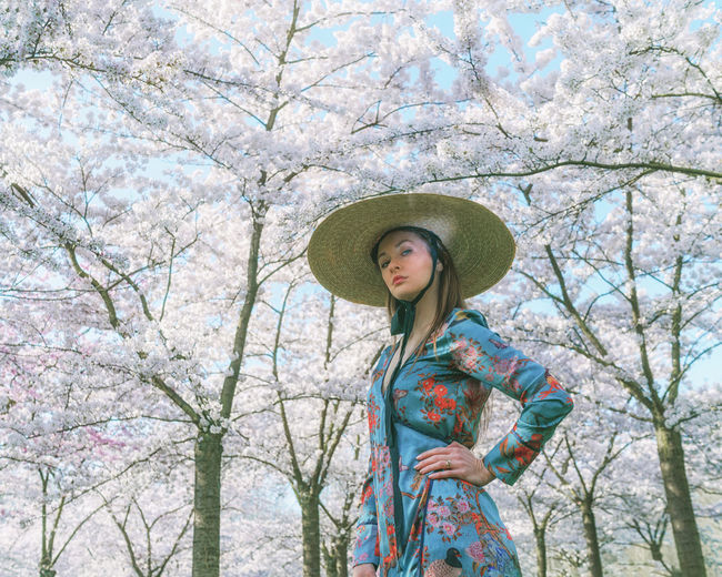 Low angle view of woman wearing hat standing against trees