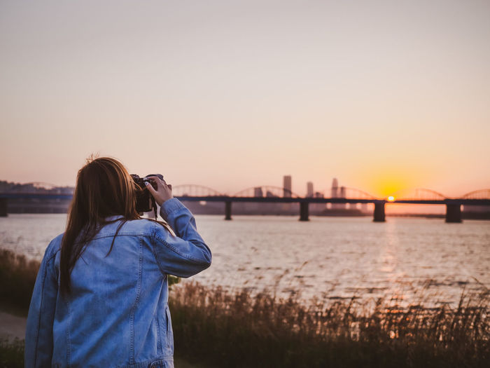 Rear view of woman photographing river during sunset