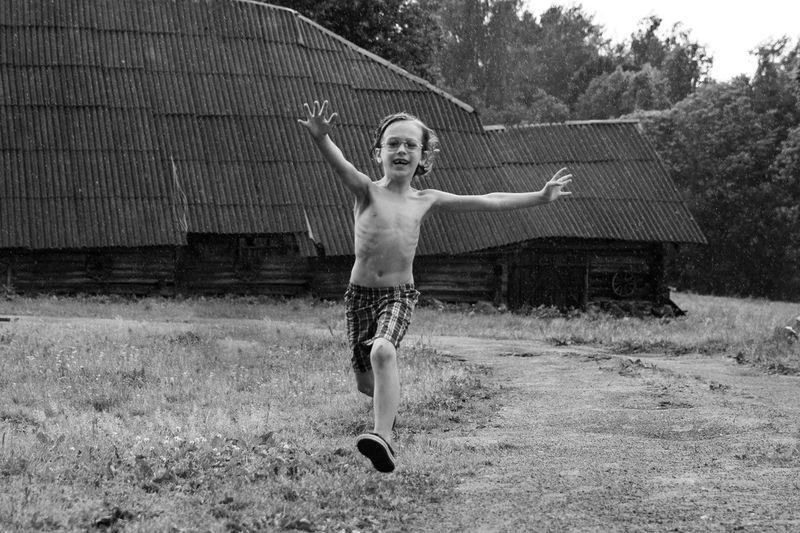 Full length of shirtless boy, running in rain