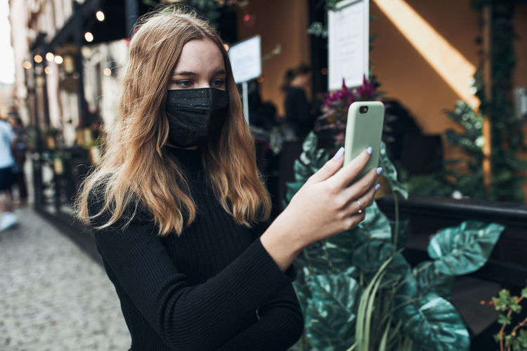 Young woman having video call talking while walking downtown wearing the face mask