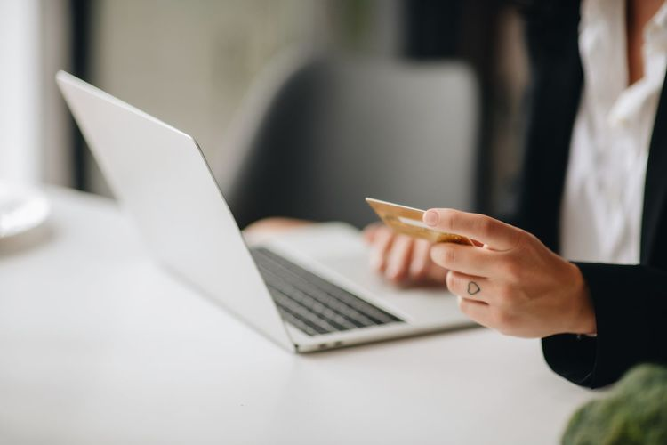 Midsection of businesswoman using mobile phone while holding credit card