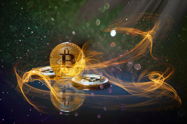 Digital composite image of bitcoins and fire