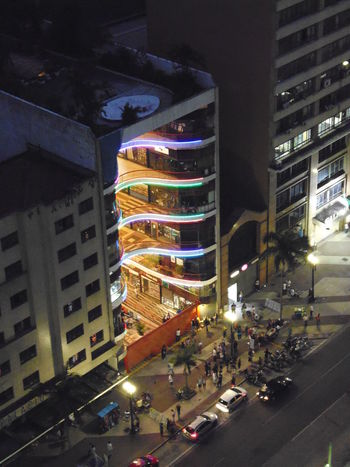 """Galeria do Rock - """"Rainbow Lights"""" Avenida São João Galeria Do Rock Night Photography Susan A. Case Sabir Unretouched Photography Architecture Building Exterior Built Structure City Cityscape Curved Architecture High Angle View Illuminated Modern Night No People Not A Drone Photo Outdoors Rainbow Lights Street Urban"""