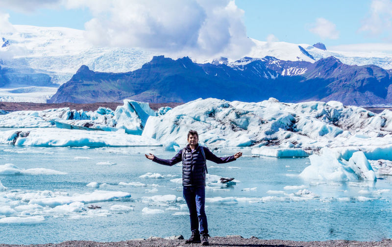 Full length of man with arms outstretched while standing against glacier