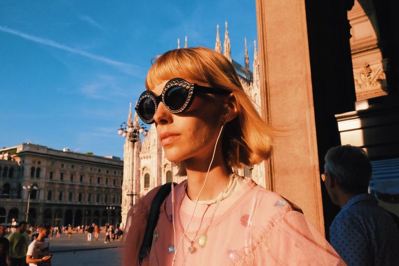 Woman wearing sunglasses in city against sky