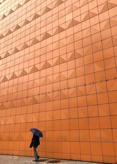 Full length of man standing against orange wall