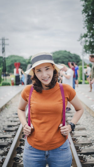 Portrait of smiling woman standing against car