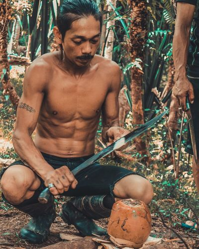 Been grateful to this man for the buko juice he made for us. #gettyimage #EyeEmNewHere #EyeemPhilippines #EyeEmPhoto #siamdiscovery The Traveler - 2018 EyeEm Awards #EyeEmSelects #eyembestshot #vscocam #vsco #siamdiscovery Moments #gettyimages #bukojuice EyeEm Selects The Portraitist - 2018 EyeEm Awards Tree Men Shirtless Sitting Working Muscular Build Holding