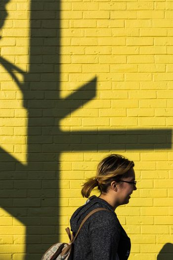 Paint The Town Yellow Shadow Real People Wall - Building Feature One Person Brick Wall Leisure Activity Sunlight Lifestyles Built Structure Day Casual Clothing Childhood Standing Architecture Outdoors Yellow Building Exterior People Adult