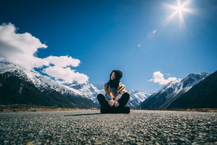 Young woman sitting on road against sky