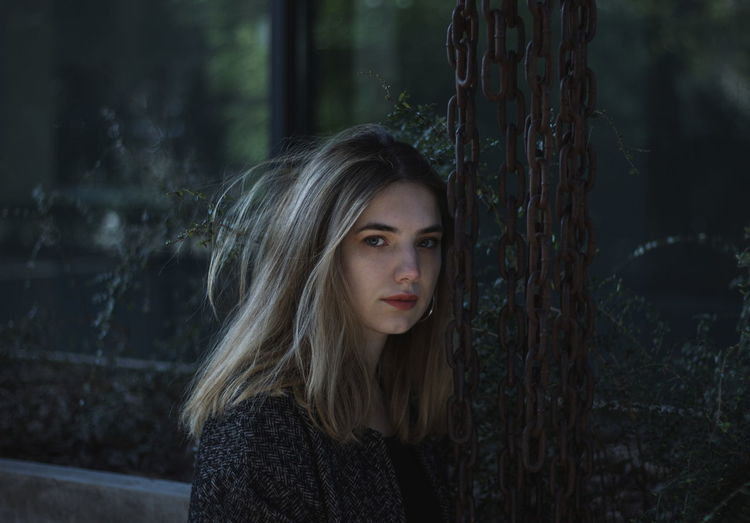 Portrait of young woman by chain against window