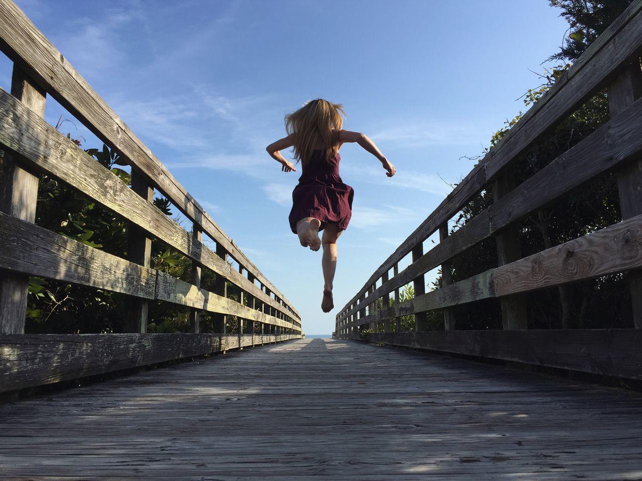 Rear view of woman jumping on footbridge against sky