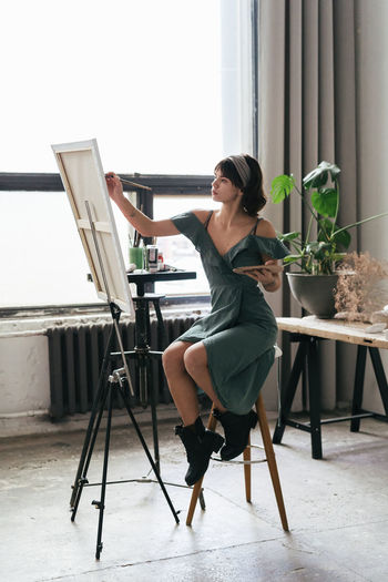 Full Length Of Woman Painting On Canvas At Art Studio