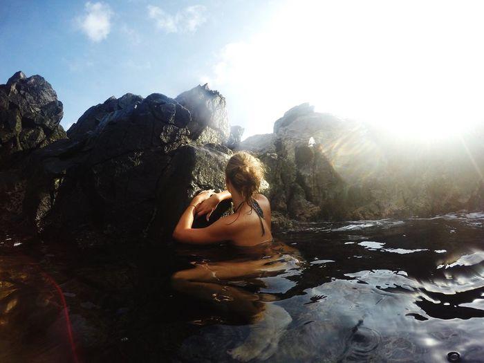 Young woman in bikini sitting on rock against sky