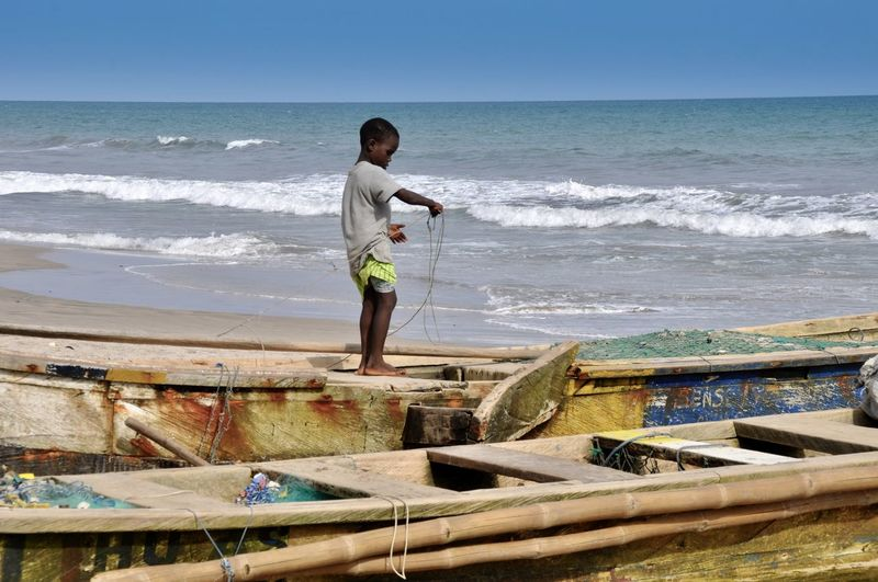 Faces Of Africa Fishing Boats Fishing Net Ghana Rope Traditional Culture Africa Beach Beauty In Nature Boy Child Childhood Horizon Horizon Over Water Motion Ocean One Person Outdoors Pirogue Playing Playing Alone Sea Shore Standing Wave
