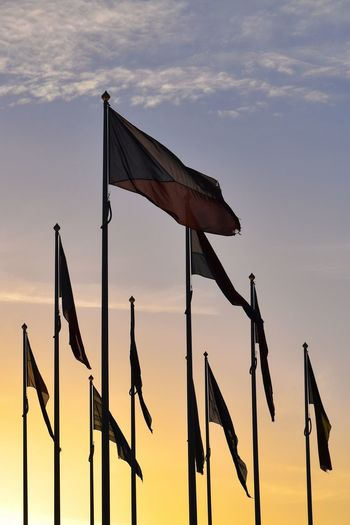 Low Angle View Of Various National Flags Against Sky During Sunset