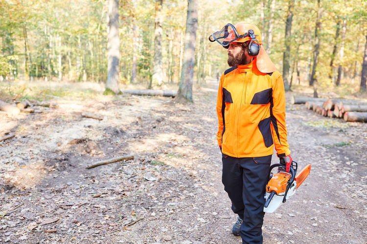Man carrying chainsaw while walking in forest
