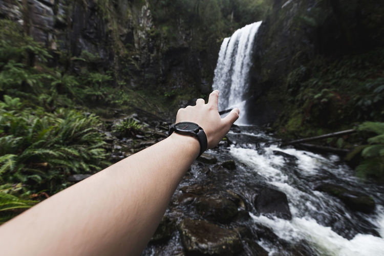 Beauty In Nature Cropped Focus On Foreground Growth Hand Nature Non-urban Scene Outdoors Person Personal Perspective Remote Scenics Tranquility Waterfall Wrist Wristwatch