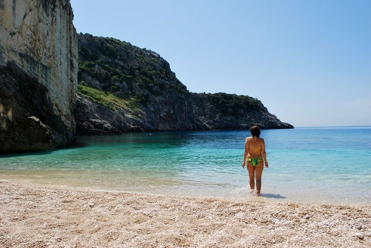 Rear view of bikini woman standing on beach against clear sky