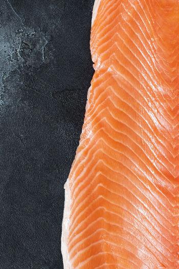 Fresh sea fish, raw salmon fillet on a black stone background. healthy oriental food
