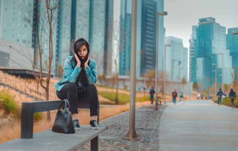 Full length portrait of young woman sitting against modern building in city