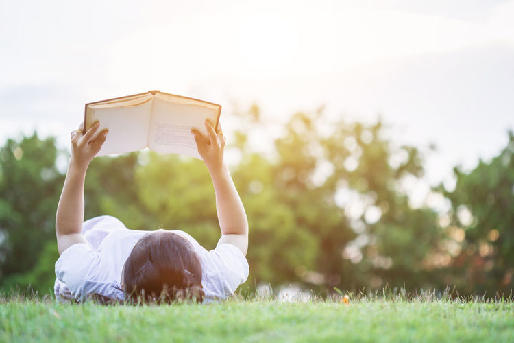 Rear view of woman reading book on field