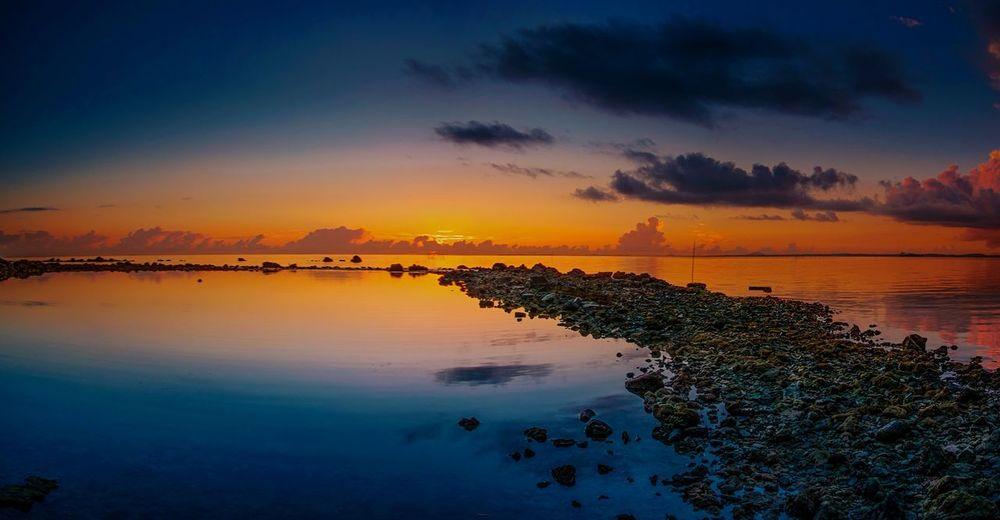 Idyllic shot of sea against orange sunset sky at batam