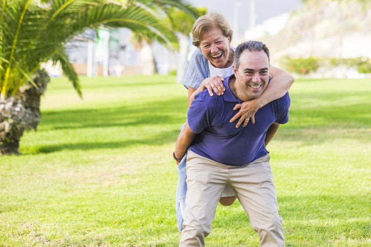 Happy Son Piggybacking Mother On Field At Public Park
