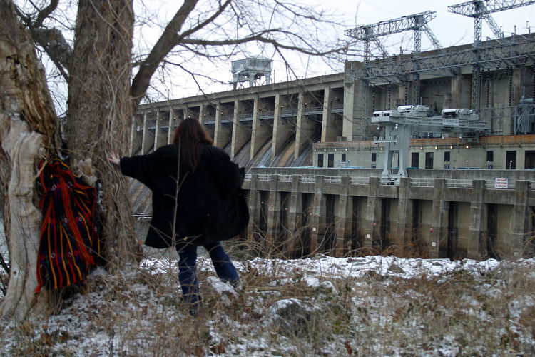 Bagnell Dam Architecture Bagnell Dam Bagnell Dam In Winter Bare Tree Built Structure City Cold Temperature Covering Day Human Figure And Technology Lifestyles Nature Outdoors Season  Sky Snow Technological Marvel And Human Marvel Warm Clothing Weather Winter Woman In Front Of Dam Wonders Of The World