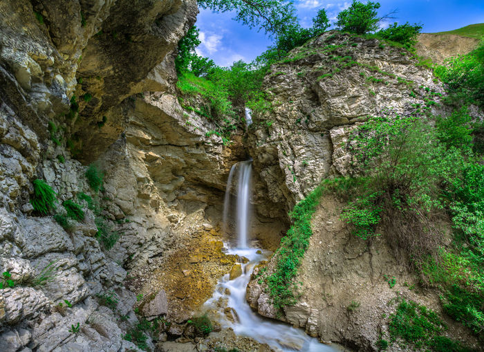 Scenic view of waterfall against rock formation