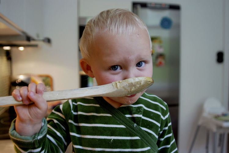 Portrait Of Cute Boy Eating Food With Wooden Spoon At Home