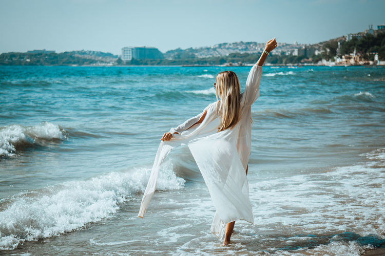 Adult Arms Raised Beach Beautiful Woman Freedom Full Length Hair Hairstyle Human Arm Land Leisure Activity Lifestyles Motion Nature One Person Real People Sea Water Women Young Adult Young Women