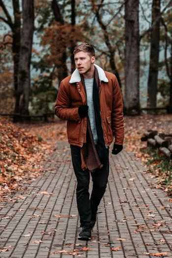 Young man walking on footpath in park during autumn