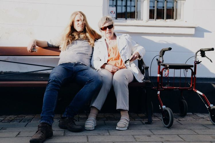 Mother and son resting on bench by mobility walker against wall during sunny day