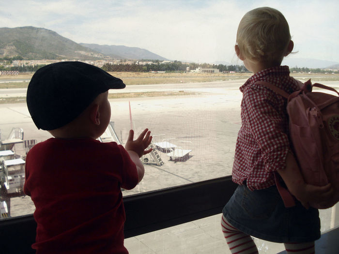 Two children looking at the tarmac through a window. Airport Ariplane Child Childhood Family Innocence Rear View Togetherness Two People