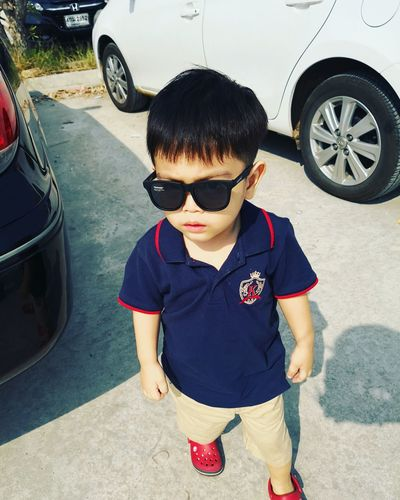 Boy wearing sunglasses standing by car