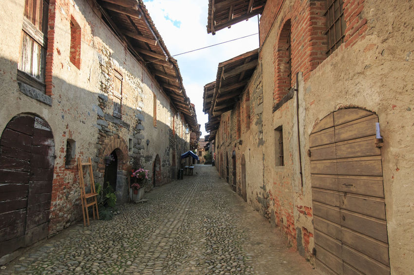 Candelo, Biella - May 4, 2016: View form the inside of the Medieval village of Ricetto di Candelo in Piedmont, used as a refuge in times of attack during the Middle Age. Alley Architecture Biella Building Building Exterior Built Structure Candelo Candelo In Fiore City City Life Day Diminishing Perspective Italy Medieval Village Narrow No People Outdoors Residential Building Residential Structure Ricetto Di Candelo  Sky The Way Forward Town Vanishing Point Walkway