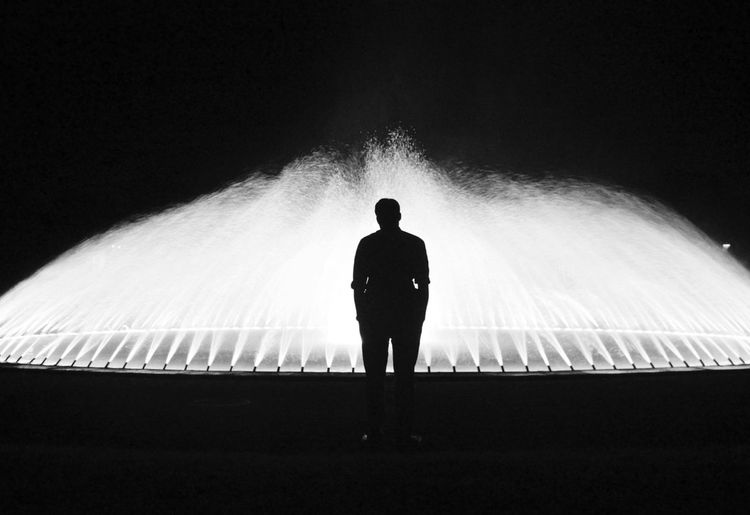 Rear view of silhouette man standing in front of fountain at night