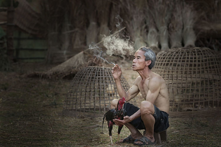 Full Length Of Shirtless Man Smoking Cigarette With Roaster On Field