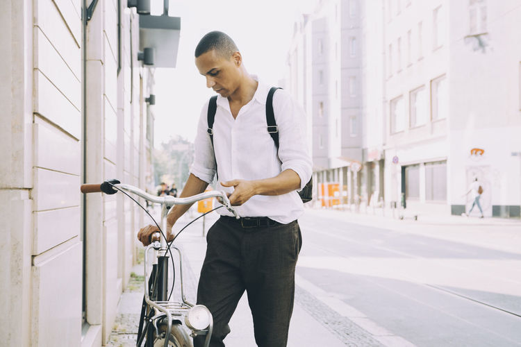 Man looking at bicycle in city