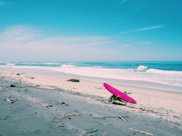 Beach Beauty In Nature Blue Calm Coastline Day Horizon Over Water Multi Colored Nature Non-urban Scene Outdoors Pink Color Remote Sand Scenics Sea Shore Sky Surfboard Tranquil Scene Tranquility Vacations Water Water Sport Wave