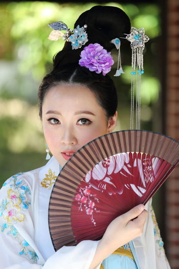 Portrait of young woman wearing qipao while holding hand fan