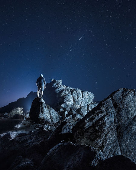 Man standing on rock against sky at night